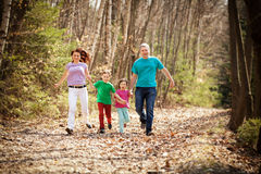Família feliz que corre nas madeiras fotografia de stock royalty free