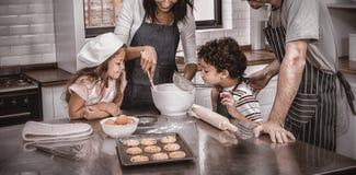 Família feliz que cozinha biscoitos junto imagem de stock royalty free