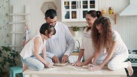 A família feliz que cozinha na cozinha, mãe prepara a massa cozendo, movimento lento
