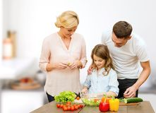 Família feliz que cozinha a salada vegetal para o jantar Imagens de Stock Royalty Free