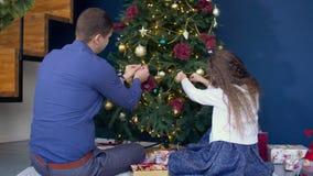 Família feliz que decora a árvore de Natal em casa filme