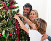 Família feliz que decora uma árvore de Natal Imagens de Stock Royalty Free