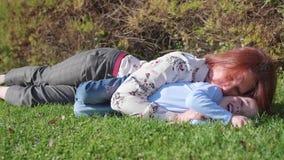 Família feliz que descansa no gramado A mãe com ternura e amor abraça sua criança, os risos do filho Infância feliz filme