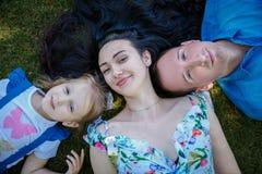 Família feliz que encontra-se na grama fotos de stock