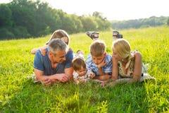 Família feliz que encontra-se na grama imagens de stock