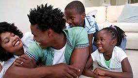 Família feliz que encontra-se no assoalho vídeos de arquivo
