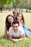 Família feliz que encontra-se no campo de grama no parque imagens de stock