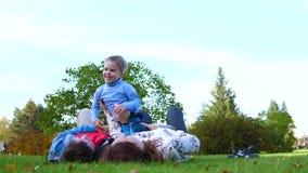 Família feliz que encontra-se no gramado A mãe e o pai que guardam seu filho em seus braços sobre sua cabeça, a criança sorriem E filme