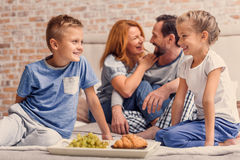 Família feliz que encontra-se para baixo na cama em casa Foto de Stock