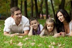 Família feliz que encontra-se para baixo no jardim imagem de stock
