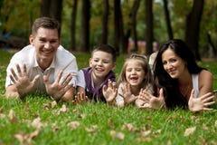 Família feliz que encontra-se para baixo no jardim fotografia de stock