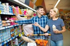 Família feliz que escolhe produtos láteos e sorriso Foto de Stock Royalty Free