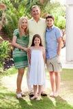 Família feliz que está junto em seu quintal imagem de stock