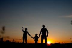 Família feliz que está no parque no tempo do por do sol Conceito da família amigável imagem de stock