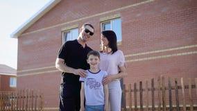 Família feliz que está perto de sua casa no dia de verão ensolarado que abraça-se Pai, mãe e filho sentindo contentes video estoque