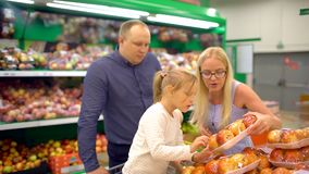 Família feliz que faz a compra Família de quatro pessoas que passa a seção do fruto na alameda A família faz compras no supermerc video estoque