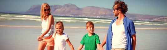 Família feliz que guarda as mãos ao andar na praia fotografia de stock