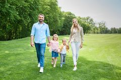 família feliz que guarda as mãos e que sorri na câmera ao andar junto foto de stock