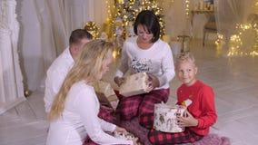 Família feliz que guarda a caixa disponivel do presente de Natal no fundo decorativo da árvore video estoque