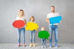 Família feliz que guarda a placa de papel colorida da bolha do discurso imagens de stock royalty free