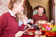 Família feliz que janta no Natal em um fundo festivo borrado Comemorando o conceito da ação de graças Ano novo feliz Fotografia de Stock Royalty Free
