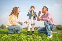 Família feliz que joga ao ar livre fotografia de stock