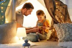 Família feliz que joga com o brinquedo na barraca das crianças em casa fotos de stock royalty free