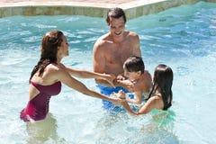 Família feliz que joga em uma piscina Fotos de Stock