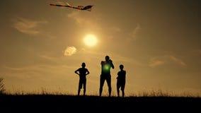 Família feliz que joga fora, voo do papagaio do voo Silhueta das crianças com um papagaio no por do sol Trabalho da equipe, jogo  filme