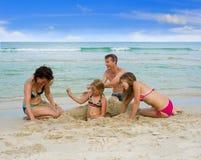 Família feliz que joga na praia Imagem de Stock