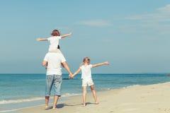 Família feliz que joga na praia no tempo do dia Fotografia de Stock Royalty Free