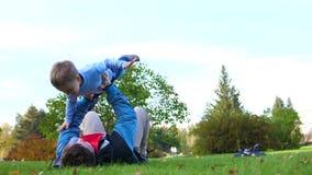 Família feliz que joga no gramado Um pai loving novo levantou a elevação da criança acima de sua cabeça, os sorrisos da criança a video estoque