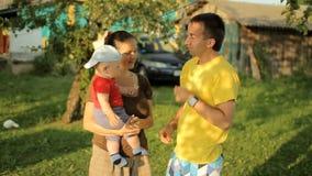Família feliz que joga no jardim com pregadores de roupa Mamã, paizinho, filho, sorriso e riso vídeos de arquivo