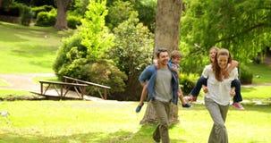 Família feliz que joga a perseguição no parque junto