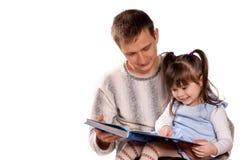 Família feliz que lê um livro Fotos de Stock Royalty Free