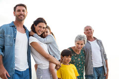 Família feliz que levanta na praia imagem de stock