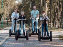 Família feliz que monta 'trotinette's bondes no parque fotografia de stock royalty free