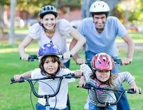 Família feliz que monta uma bicicleta fotos de stock royalty free