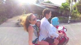 Família feliz que monta uma motocicleta nos trópicos Um dia ensolarado brilhante Phangan, Tailândia vídeos de arquivo
