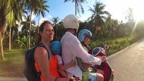 Família feliz que monta uma motocicleta nos trópicos Um dia ensolarado brilhante Phangan, Tailândia filme