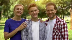 Família feliz que olha a câmera, orgulhosa de seu filho, programa da troca do estudante imagem de stock