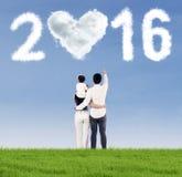 Família feliz que olha os números 2016 Imagem de Stock
