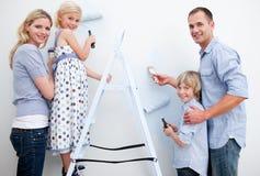 Família feliz que pinta um quarto com escovas Foto de Stock