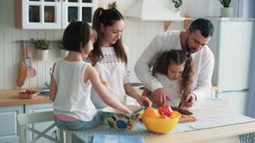 Família feliz que prepara o alimento na cozinha, cortando vegetais, movimento lento