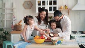 Família feliz que prepara o alimento na cozinha, cortando vegetais, movimento lento vídeos de arquivo