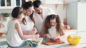 Família feliz que prepara a salada na cozinha, cortando vegetais, movimento lento
