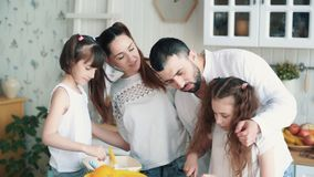 Família feliz que prepara a salada na cozinha, cortando vegetais, movimento lento video estoque
