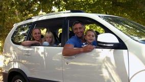 Família feliz que prepara-se para a viagem por estrada e que olha a câmera vídeos de arquivo