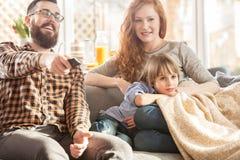 Família feliz que presta atenção à tevê junto Foto de Stock