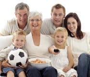Família feliz que presta atenção a um fósforo de futebol em casa Imagens de Stock
